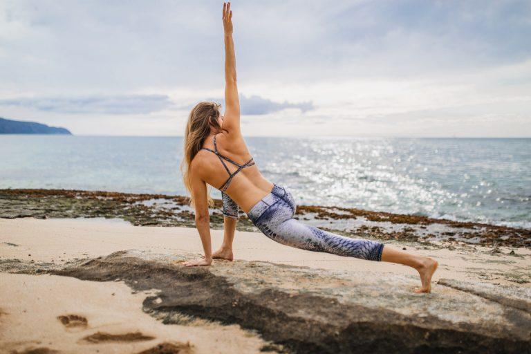 Tânără poartă pantaloni de yoga pe plajă